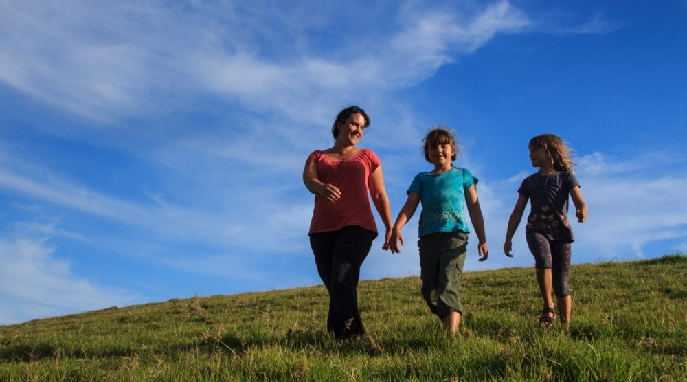 Home banner image family walking on a grassy hill