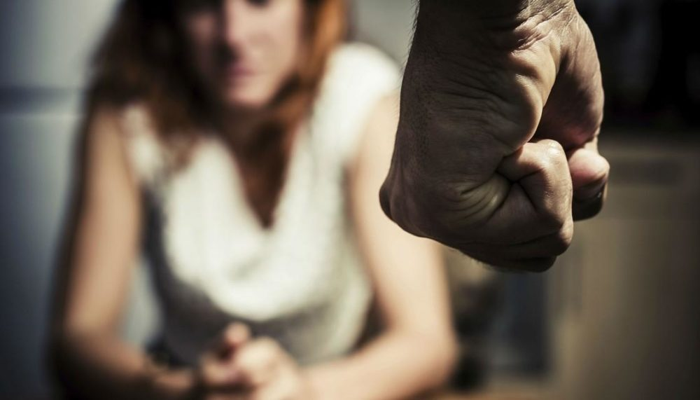 Clenched fist threatens woman sitting down