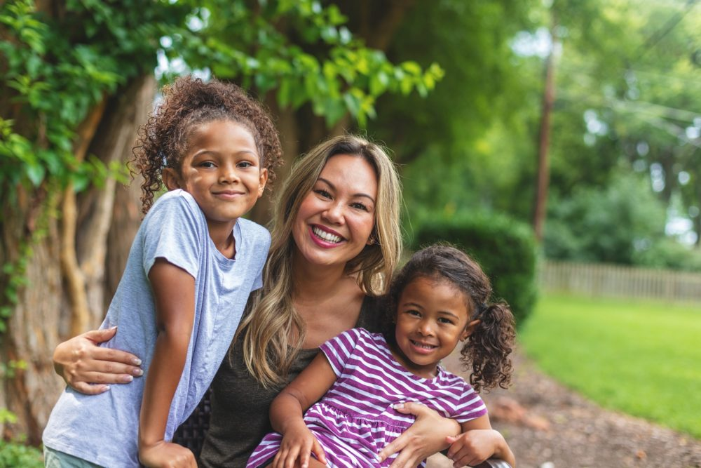 Mother with two daughters of mixed Chinese and African American ethnicity in a green lush back yard setting posing for portraits smiling and being silly