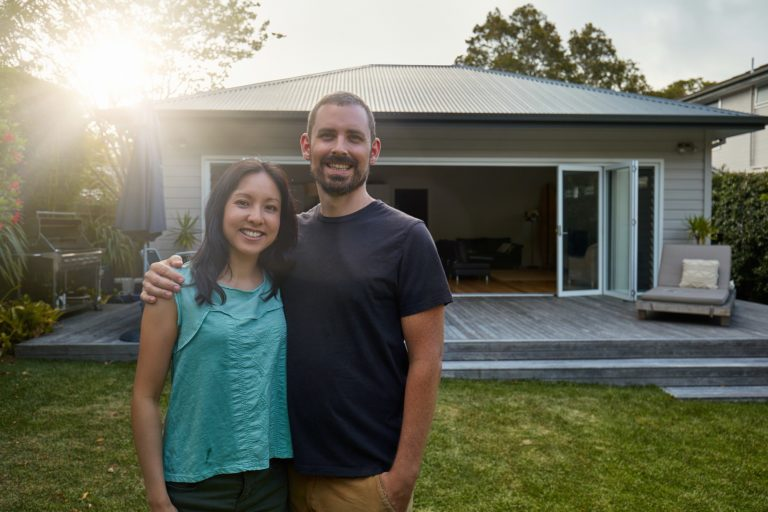Portrait of smiling mid adult couple standing against house during sunset. Happy man and woman are in lawn at back yard. They are in casuals.