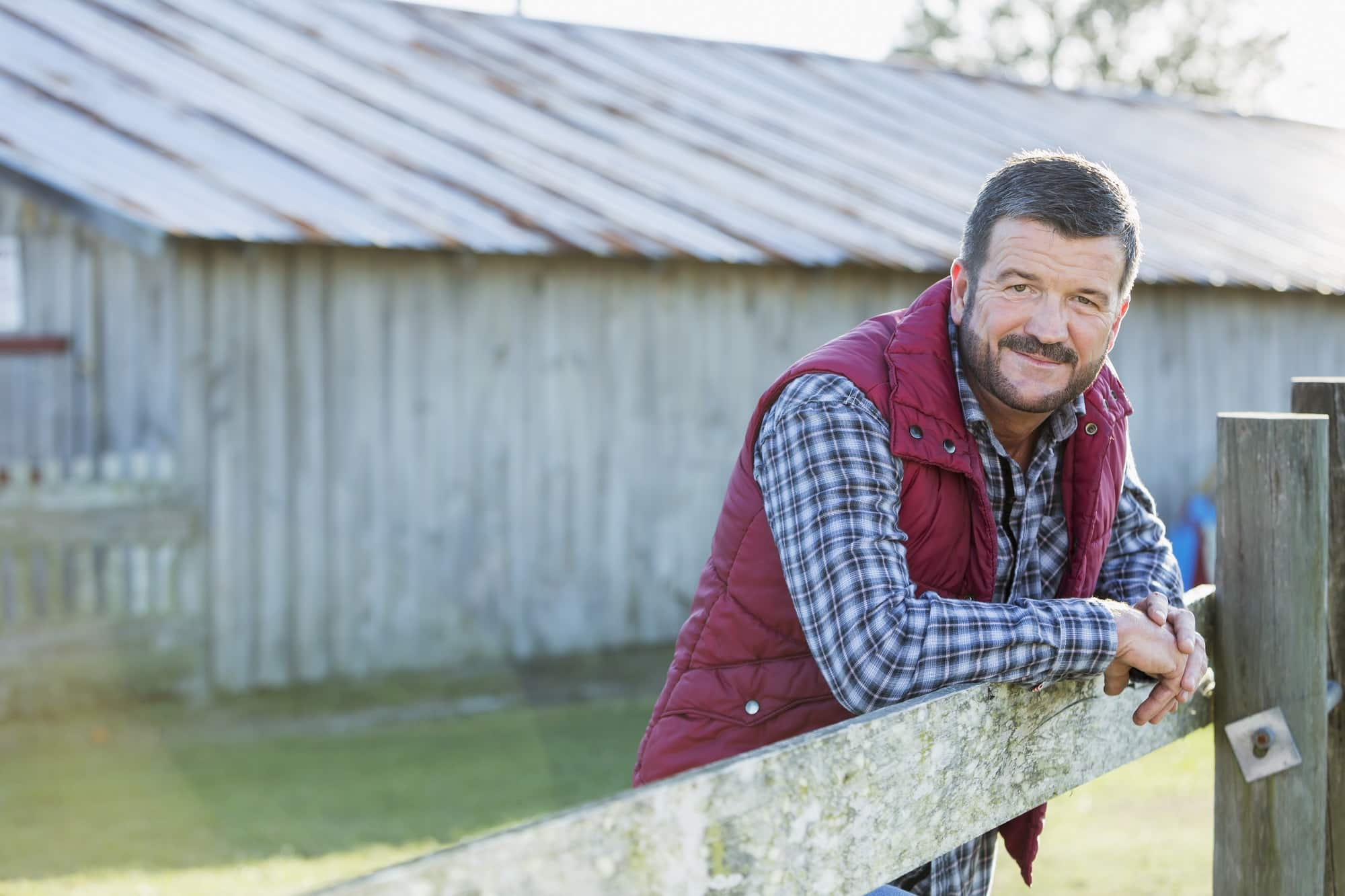 A farmer or rancher, mature man in his 50s, standing outside a barn, with his arms leaning on a wooden fence. He is wearing jeans, boots, a plaid shirt and vest.