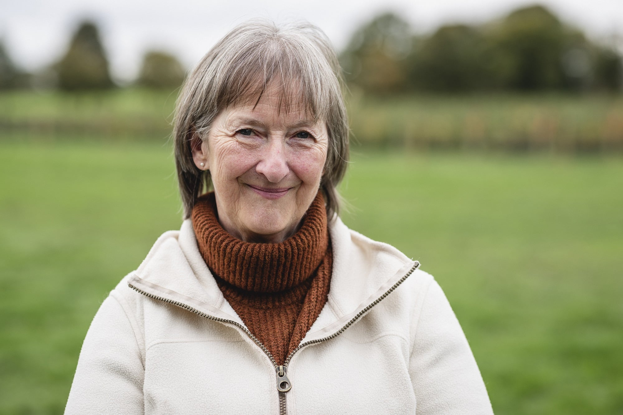 Portait of a senior woman standing in a field while at a farm in Autumn, smiling while looking at the camera.