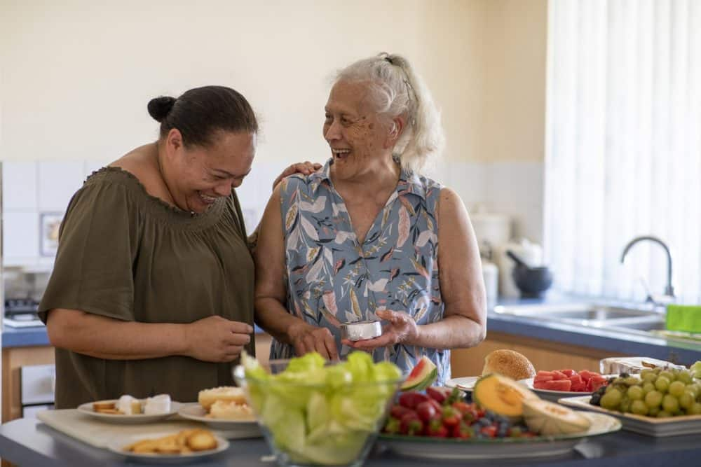 Senior Pacific Islander woman and her mature daughter preparing food together in their kitchen at home.