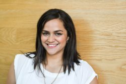 Happy, young, Maori female wIth shoulder length dstk haIr in busIness attIre on her own and against a wooden background