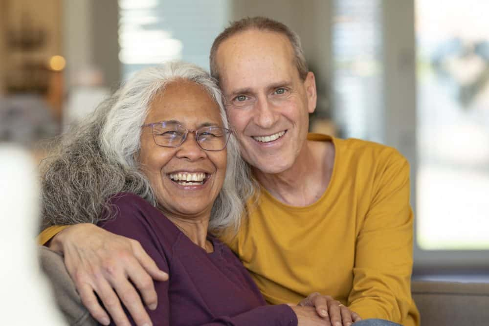 Portrait of a vibrant senior couple embracing while relaxing together at home.