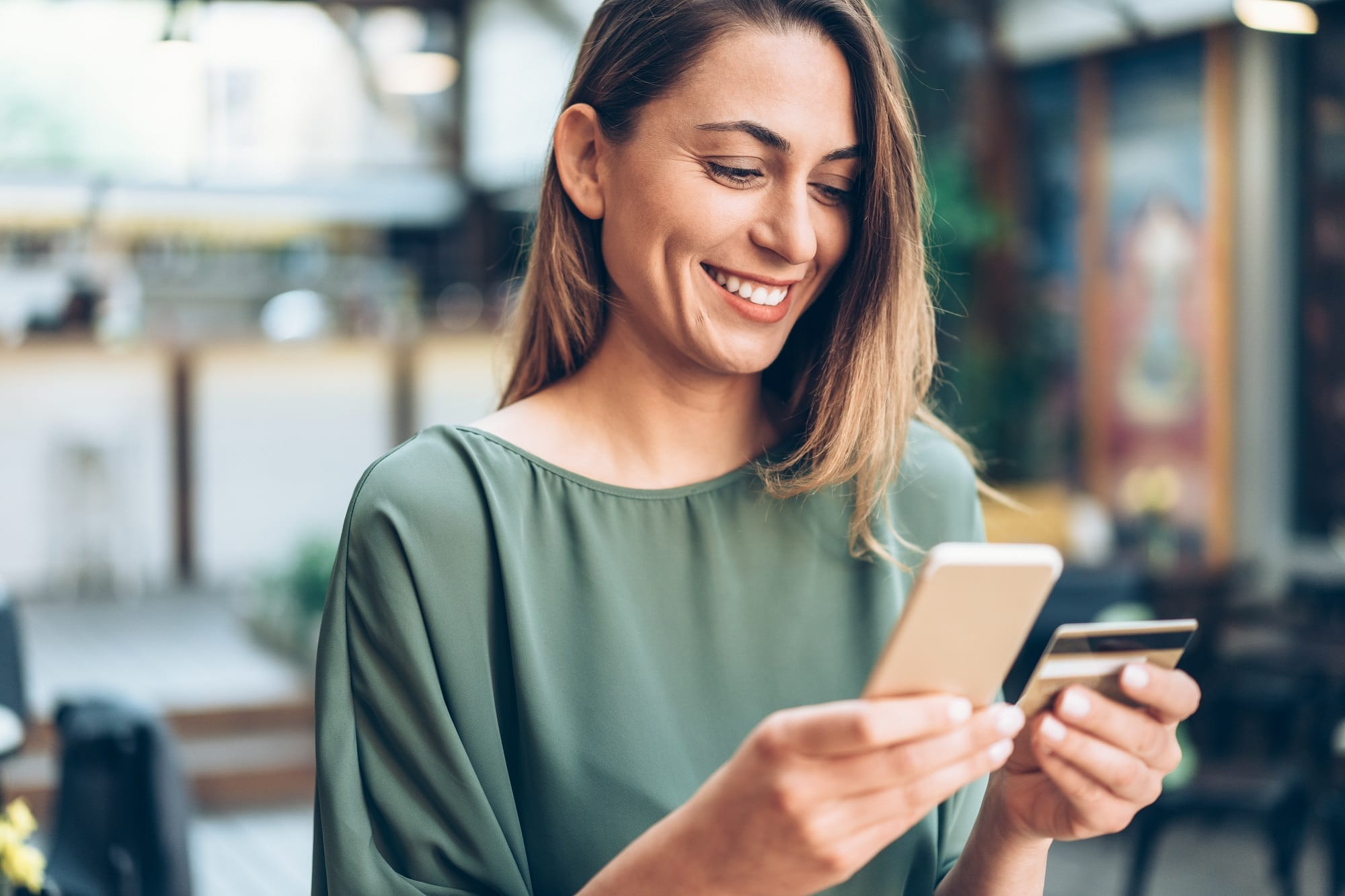 Young woman shopping online in cafe using smartphone and credit card