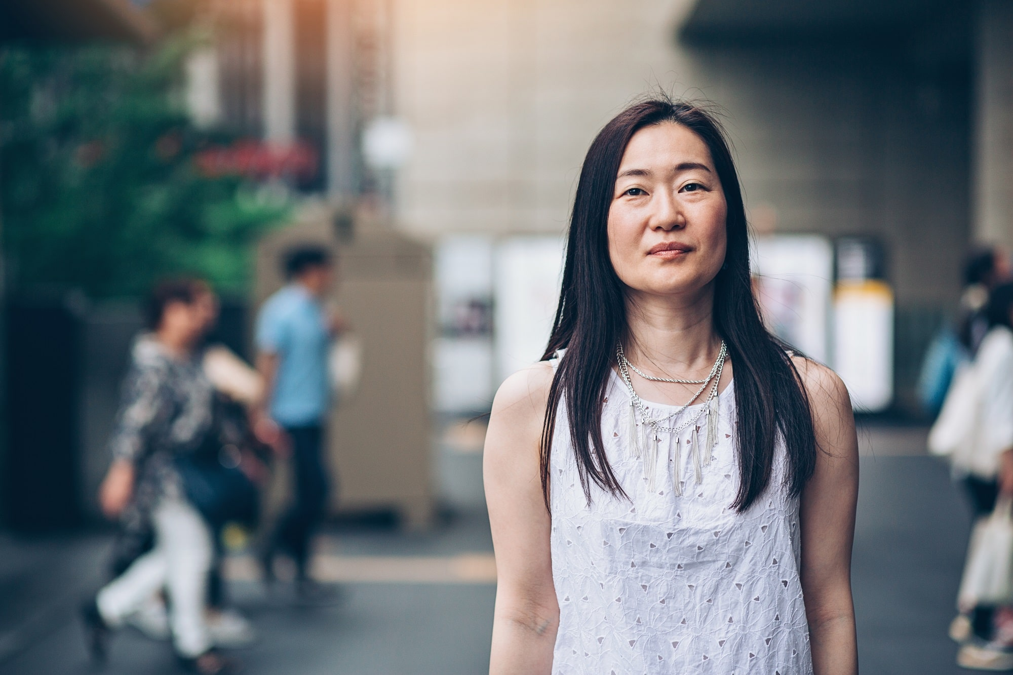Portrait of a middle aged Japanese woman standing outdoors with arms crossed