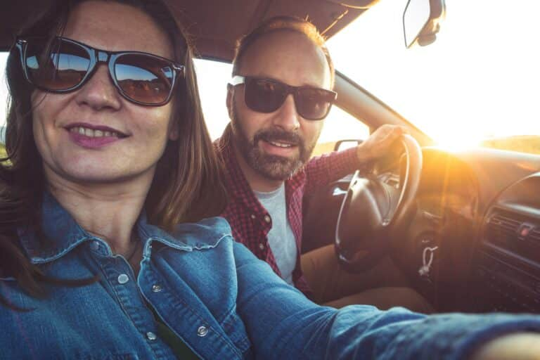 Photo of the couple traveling in the car taking selfie