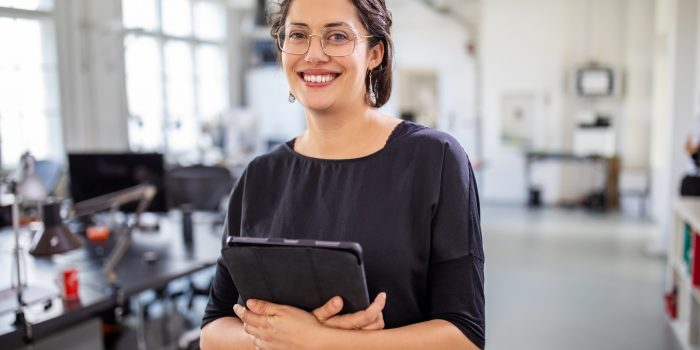 Portrait of a mature businesswoman holding a digital tablet in office. Smiling female professional standing at modern workplace.